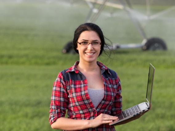 A woman holds a laptop while standing in a green agricultural field with a sprinkler system in the background.