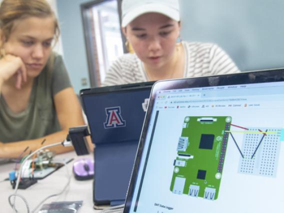 Two female University of Arizona students working at a computer.