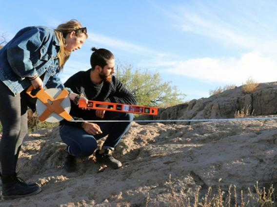 Two University of Arizona students work outdoors to survey the environment.