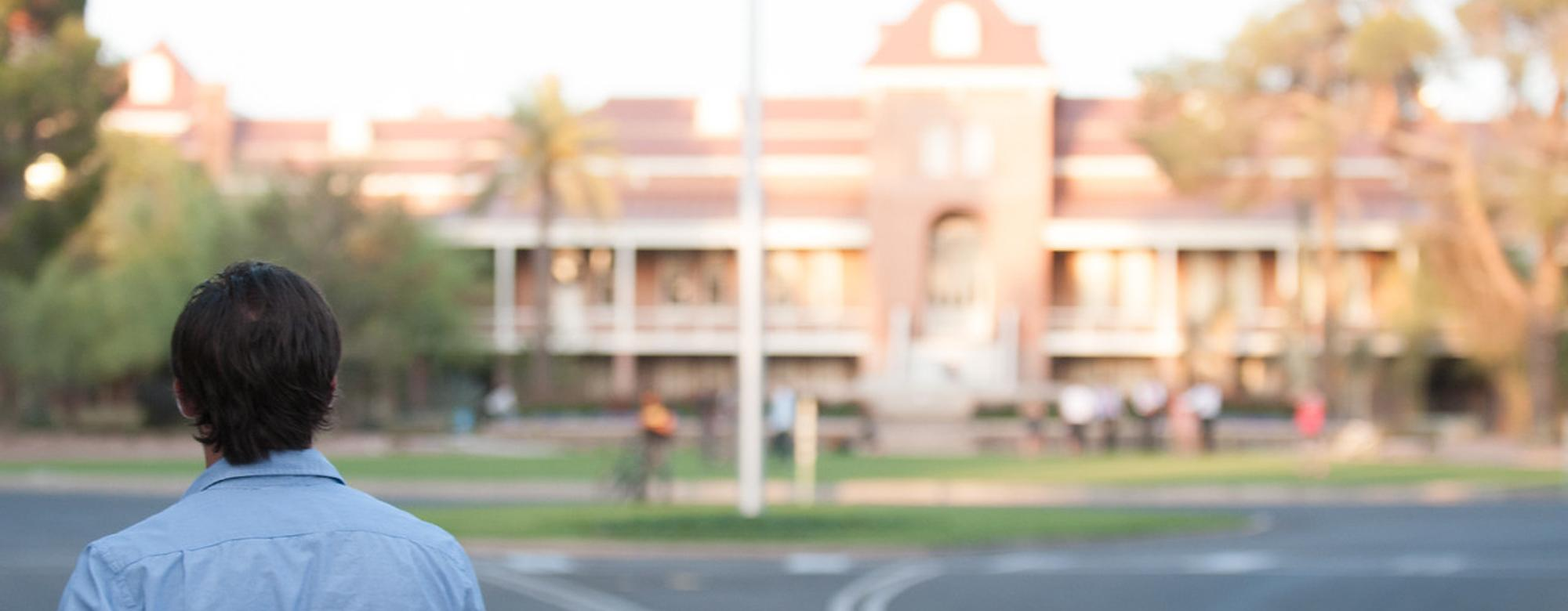 A transfer student stands facing Old Main at the University of Arizona